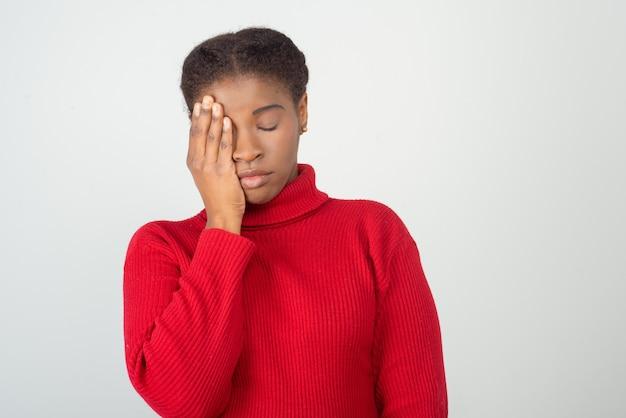 Wyczerpana młoda kobieta trzyma rękę na głowie