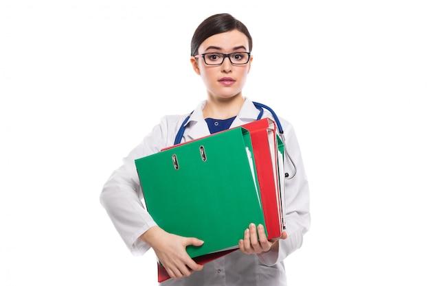 Wyczerpana młodej kobiety lekarka z stetoskopu mienia segregatorami w jej rękach w bielu mundurze