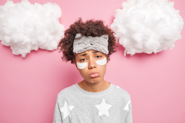 Wyczerpana niezadowolona smutna etniczna kobieta o kręconych włosach ma zmęczony wygląd po pracowitym dniu nosi maskę do spania poddaje się zabiegom na twarz nakłada kolagenowe płatki odizolowane na różowej ścianie