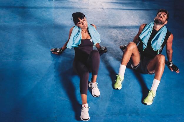 Wyczerpana para na podłodze w siłowni