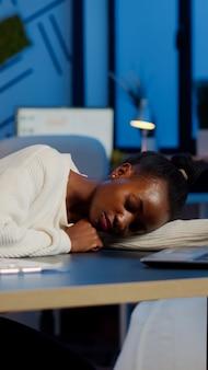 Wyczerpana przeciążenie zasypia afrykańska kobieta biznesu