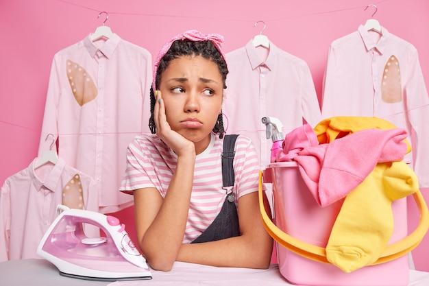 Wyczerpana, smutna, etniczna gospodyni domowa pozuje w pobliżu deski do prasowania z koszem na pranie, używa żelazka elektrycznego, ma dużo pracy do wykonania, stoi na prasowanych ubraniach w ścianie