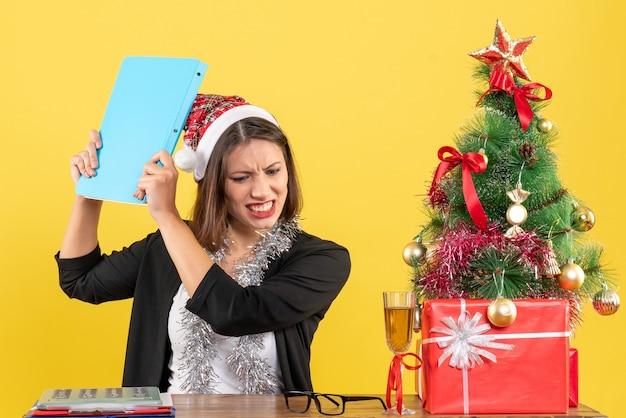 Wyczerpana urocza dama w garniturze z czapką świętego mikołaja i dekoracjami noworocznymi trzyma dokument w biurze na żółto na białym tle