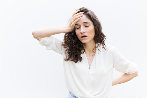 Wyczerpana zmęczona kobieta z zamkniętymi oczami, dotykając głowy