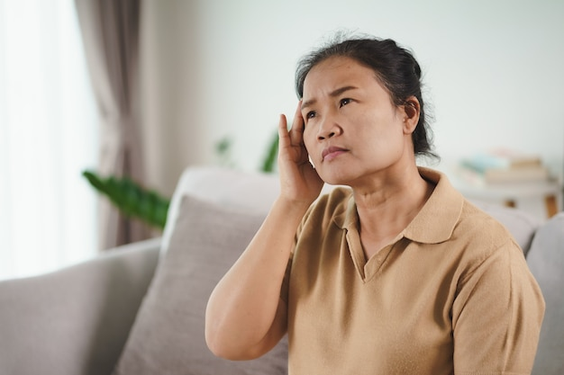 Wyczerpana, zmęczona, przygnębiona, zestresowana zamyślona dojrzała starsza kobieta cierpiąca na bóle głowy, choroby mózgu, problemy psychiczne, alzheimer concept.