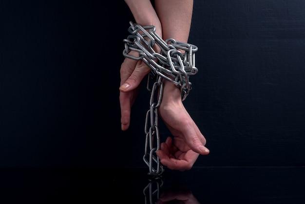 Wyczerpane kobiece dłonie z opuchniętymi żyłami związane z wiszącymi metalowymi łańcuchami