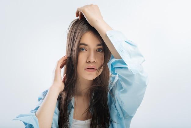 Wyczerpane życie. odblaskowa piękna, dobrze wyglądająca kobieta, wpatrzona w proste i dotykające włosów, zagubiona w snach