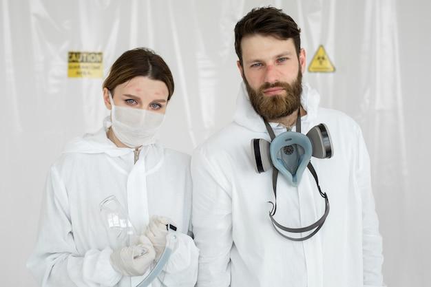 Wyczerpani lekarze lub pielęgniarki biorący mundur z ochronną maską. coronavirus covid-19 outbrek. stan psychiczny lekarza. przepracowani pracownicy służby zdrowia ze łzami w oczach