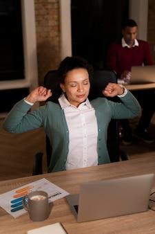 Wyczerpani ludzie w biurze pracujący do późna