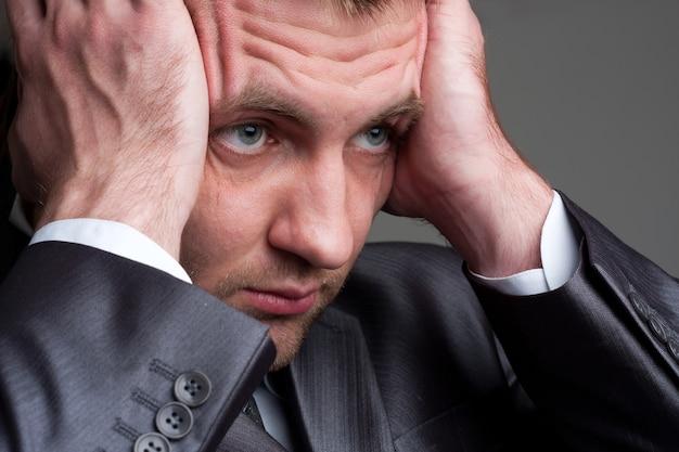 Wyczerpany biznesmen smutny trzymając głowę