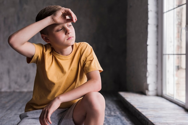 Wyczerpany chłopiec z ręką na czole
