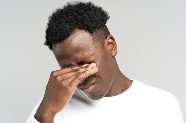 Wyczerpany czarny mężczyzna chce zasnąć, pocierając oczy, czuje zmęczenie po przepracowaniu przy laptopie
