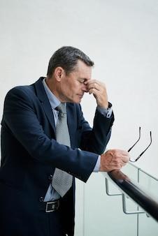 Wyczerpany dojrzały biznesmen rasy kaukaskiej z zamkniętymi oczami pociera grzbiet nosa, czując zmęczenie oczu po długim noszeniu okularów