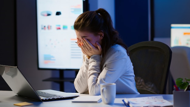 Wyczerpany freelancer śpiący przed laptopem pracujący w nowoczesnym biurze firmy startowej późno w nocy. zestresowany pracownik korzystający z nowoczesnej technologii bezprzewodowej sieci robi w godzinach nadliczbowych zamykając oczy.