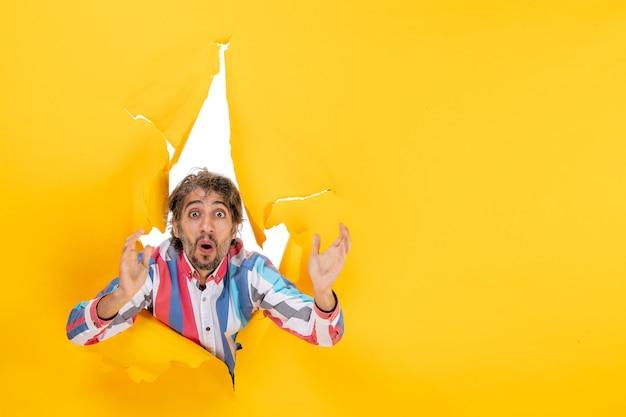 Wyczerpany i emocjonalny młody człowiek patrzący na coś w rozdartym żółtym tle dziury w papierze