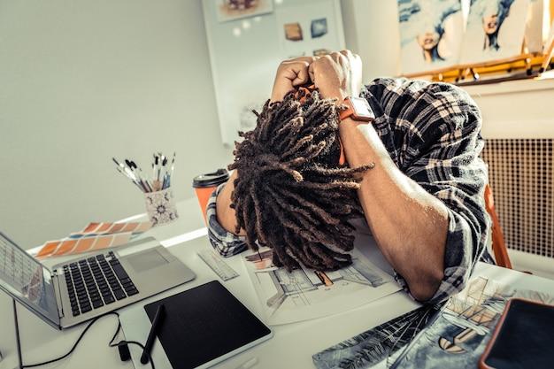 Wyczerpany i zmęczony. zaniepokojony projektant wnętrz, który nie ma nowych pomysłów, czuje się wyczerpany i zmęczony