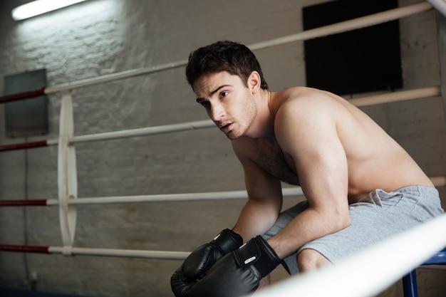 Wyczerpany mężczyzna bokser siedzi na ringu i myślenia