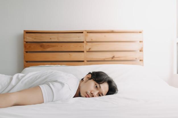 Wyczerpany mężczyzna leżał na łóżku, czując wypalenie
