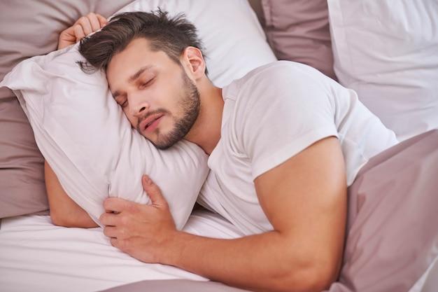 Wyczerpany mężczyzna śpi w swoim łóżku