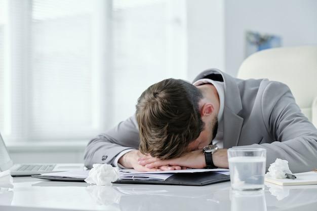 Wyczerpany młody biznesmen leżący na stole z papierami i pogniecionymi serwetkami, cierpiący na ból głowy