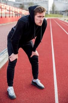 Wyczerpany młody mężczyzna sportowiec stojący na torze wyścigowym