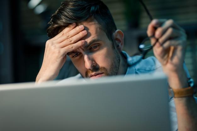 Wyczerpany pracownik korzysta z laptopa