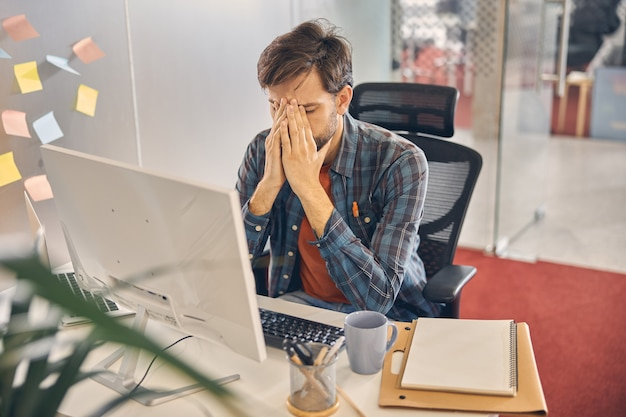 Wyczerpany pracownik płci męskiej siedzi przy stole z komputerem i chowa głowę w dłoniach