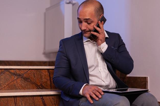 Wyczerpany, przepracowany biznesmen rozmawia przez telefon z zespołem o terminie projektu. przedsiębiorca pracujący do późnych godzin wieczornych siedzi na schodach w biurze budynku.