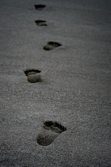 Wyczyść ludzkie ślady na czarnym piasku u wybrzeży