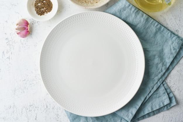 Wyczyść pusty biały talerz na białym kamiennym stole, skopiuj przestrzeń, makietę, widok z góry.