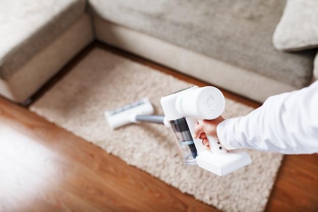Wydajny bezprzewodowy odkurzacz z technologią białego cyklonowego odpylania w dłoni, odkurza dywan w domu w pobliżu sofy.