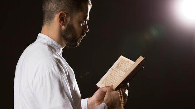 Wydarzenie ramadam i arabski mężczyzna czytający środek strzału