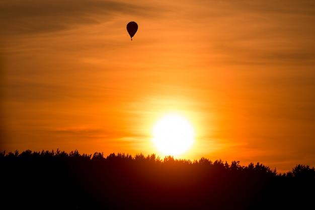 Wydarzenie sportowe w niebie. lot balonem nad lasem o zachodzie słońca. spokojny kolorowy romantyczny wieczór ze światłem słonecznym w przyrodzie. zamknięty widok balon przy horyzontem.
