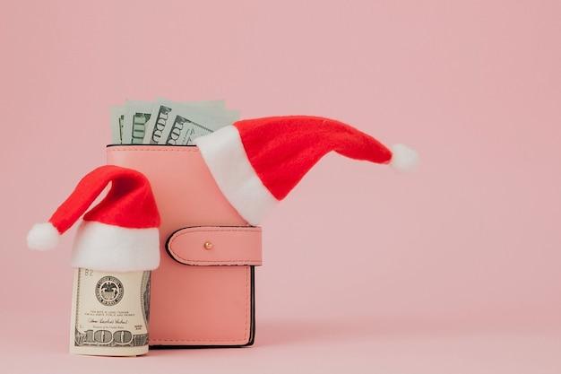 Wydatki na boże narodzenie. różowa skórzana torebka z czapką świętego mikołaja, prezentem, choinką i banknotami dolarów na różowo. świąteczne zakupy. wyprzedaż wakacyjna
