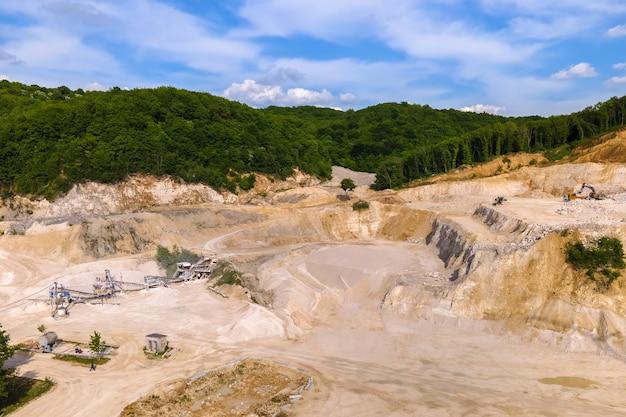 Wydobycie odkrywkowe materiałów z piaskowca budowlanego za pomocą koparek i wywrotek.