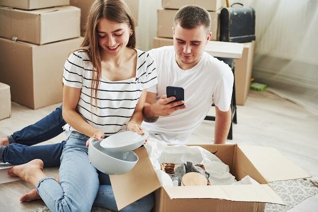 Wydobywa nowe talerze. wesoła młoda para w swoim nowym mieszkaniu. koncepcja ruchu.