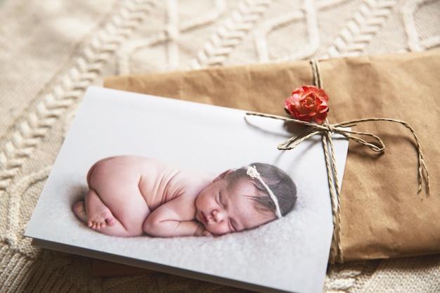 Wydrukowana kartka z życzeniami ze śpiącym noworodkiem na dzianym tle ubrania dla dzieci jesienno-zimowe