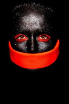 Wygląd mody. glamour fashion piękna czarna amerykanka w czarnej masce z pomarańczowym jaskrawym makijażem i pomarańczowym materiałem