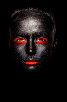 Wygląd mody. glamour fashion piękna czarna amerykanka w czarnej masce z pomarańczowym jasnym makijażem i pomarańczowymi ustami