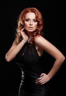 Wygląd mody. glamour portret pięknej seksownej rudej stylowej modelki młodej kobiety rasy kaukaskiej z jasnym makijażem, z idealnie czystą w czarnej sukience
