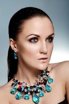 Wygląd mody. glamour portret zbliżenie model piękna brunetka kaukaska młoda kobieta o zdrowych włosach z doskonałą czystą skórą i niebieską biżuterią