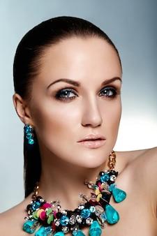 Wygląd mody. glamour portret zbliżenie piękna brunetka model kaukaskiej młodej kobiety ze zdrowymi włosami i zieloną biżuterią akcesoriów