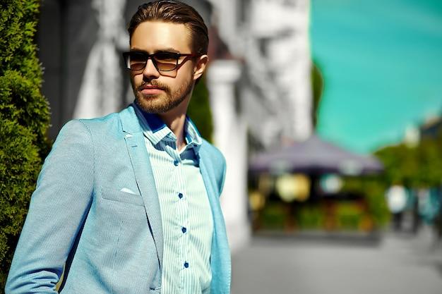 Wygląd mody. młody stylowy pewny siebie szczęśliwy przystojny biznesmen model w garnitur ubrania styl życia na ulicy w okulary przeciwsłoneczne