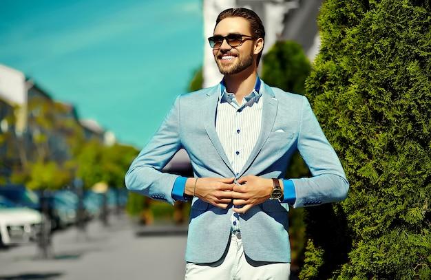 Wygląd mody. młody stylowy pewny siebie szczęśliwy przystojny biznesmen model w kolorze ubrania styl życia na ulicy w okulary przeciwsłoneczne