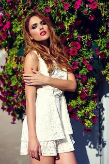 Wygląd mody. seksowny portret model piękny seksowny stylowy blond młoda kobieta z jasny makijaż i różowe usta z idealnie czystą skórę w kapeluszu w pobliżu letnich kwiatów