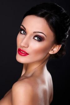 Wygląd mody. seksowny portret pięknej modelki sexy kaukaski młoda kobieta z czerwonymi ustami, jasny makijaż, z idealnie czystą skórą na czarnym tle