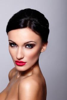 Wygląd mody. seksowny portret pięknej modelki sexy kaukaski młoda kobieta z czerwonymi ustami, jasny makijaż, z idealnie czystą skórą na szarym tle