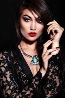 Wygląd mody. seksowny portret pięknej seksownej stylowej brunetki młodej kobiety rasy kaukaskiej z jasnym makijażem, z czerwonymi ustami, z idealnie czystą skórą z biżuterią w czarnej tkaninie