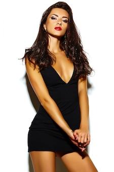 Wygląd mody. seksowny portret pięknej seksownej stylowej brunetki młodej kobiety rasy kaukaskiej z jasnym makijażem, ze zdrowymi kręconymi włosami w czarnej niebieskiej sukience w studio