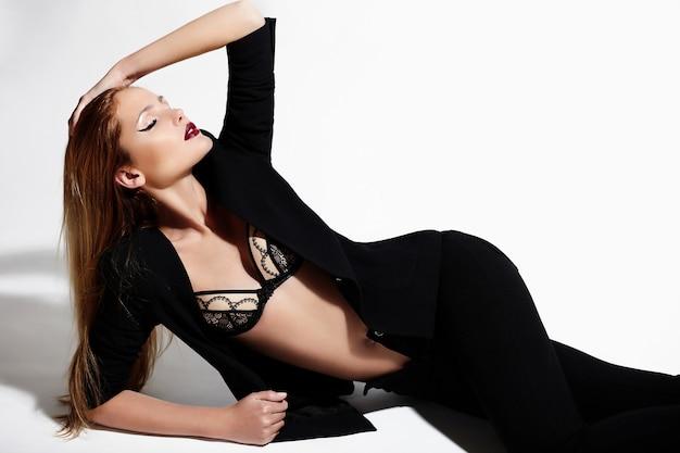 Wygląd mody. seksowny portret piękny seksowny stylowy model kaukaski młoda kobieta w czarnej tkaniny z jasnym makijażem